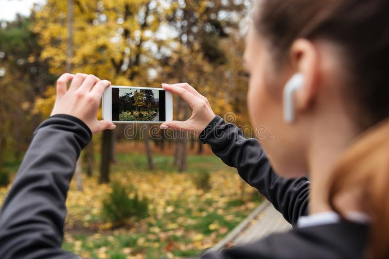 Close up of fitness woman in earphones taking a photo. While jogging at the park stock photo