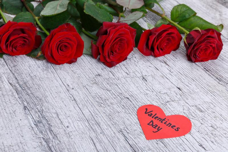 Red roses on a gray wooden background, with a heart with an inscription the day of St. Valentine, a free place for text. stock photo