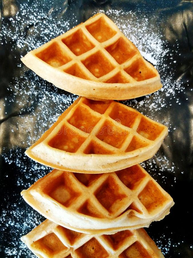 Close up flat lay of four waffles with icing sugar stock images