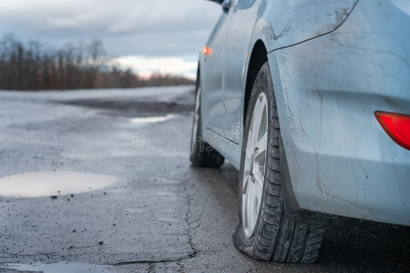 Close up Flat tire and blue car on the road after the rain waiting for repair stock photos
