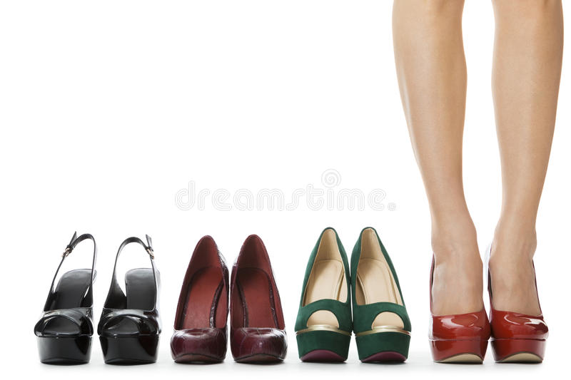 Close up Flawless Woman Legs in Glossy Red High Heel Shoes Standing. Between Other Elegant High Heels. Isolated on White Background royalty free stock images