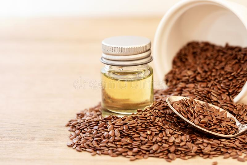 Close up flaxseed essential oil and seeds in a wooden spoon , Heart healthy food which superfood and rich of omega 3 stock images