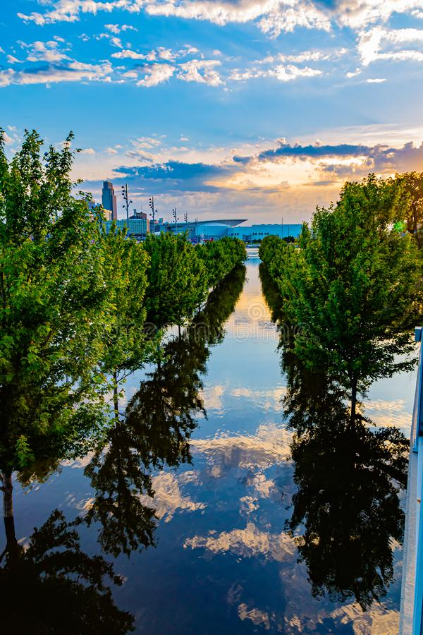 Close up of sky, cloud and tree reflections in 2019 Missouri River flooding of Tom Hanafan River`s Edge Park. Close up of flooded field with reflections of the stock photography