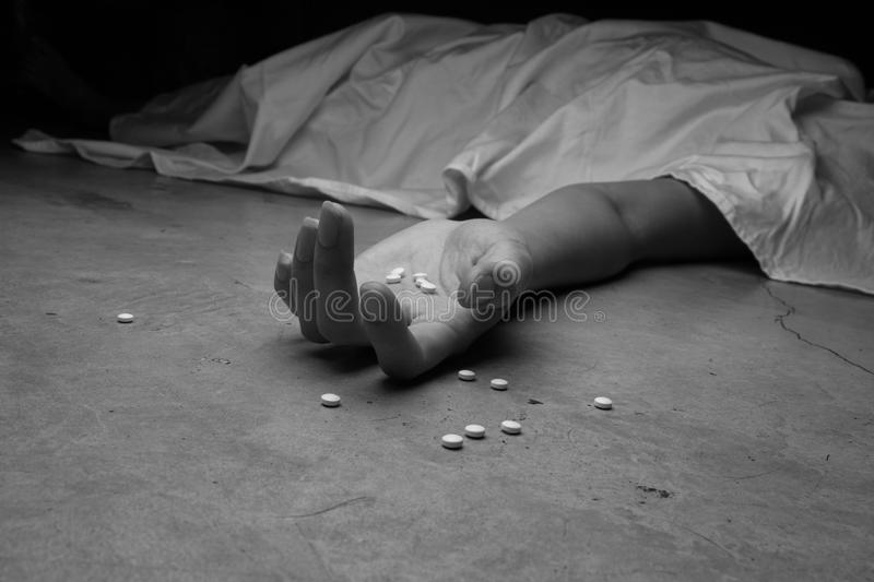 Close-up on the floor of the drugs in hand of the dead body. stock photos