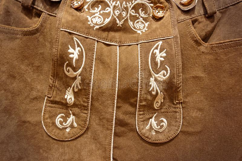 Close up of floral pattern stitched on traditional german `Lederhosen` leather breeches. Heidelberg, Germany - July 2019: Close up of floral pattern stitched on royalty free stock photography