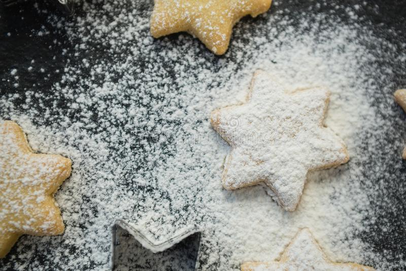 Close up of flour over star shape cookies stock photo