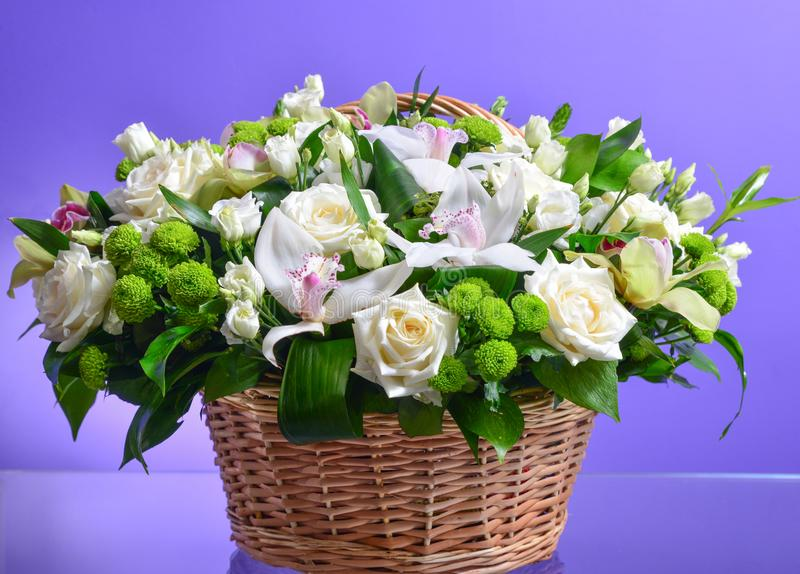 Close up flower bouquet arrangement in wicker basket  on white, carnation, rose, orchid, anunculus.  royalty free stock photo