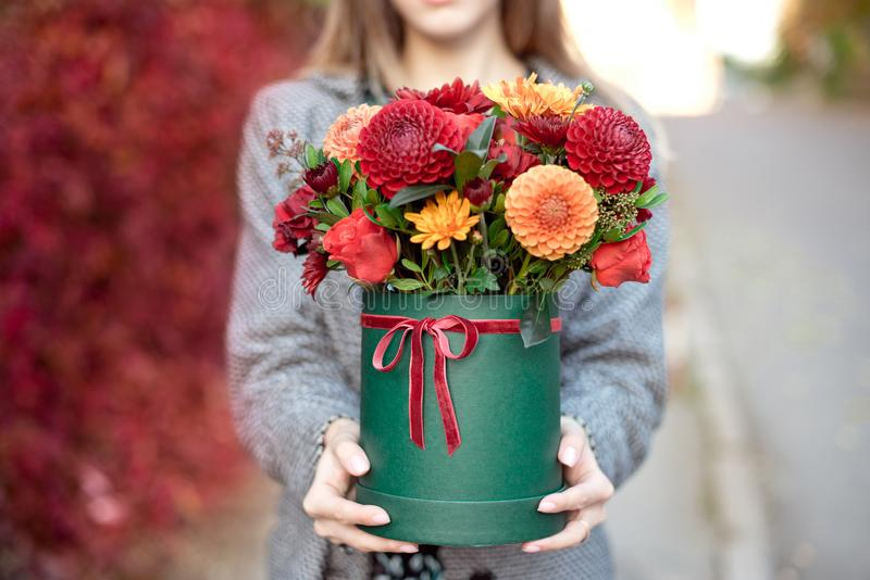 Close-up flower-box in woman hands as a gift concept for wedding, birthday, event, celebration, flowers delivery. Surprise stock image