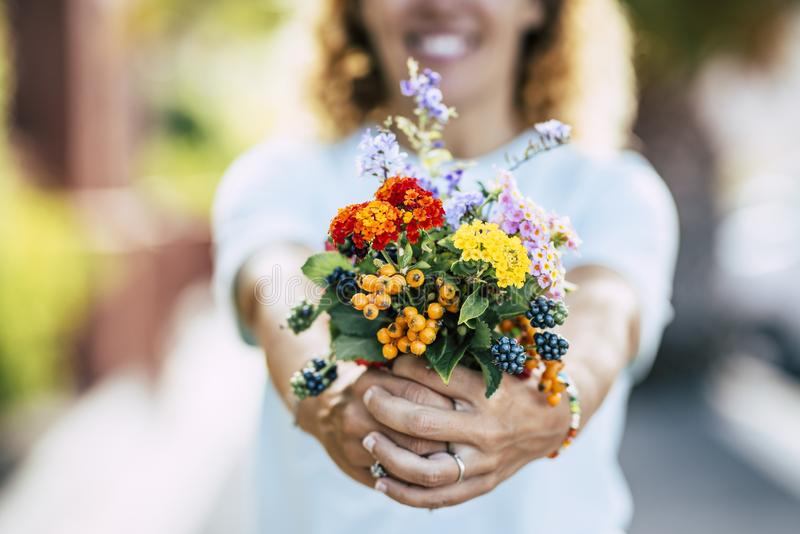 Close up of flowers bouquet and cheerful caucasian woman defocused in background - colors and earth planet environment respect. Concept - people and nature love stock image