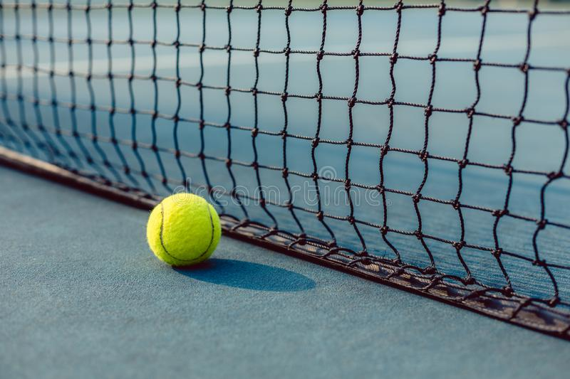 Close-up of a fluorescent yellow ball in front of the net of a tennis court royalty free stock photo