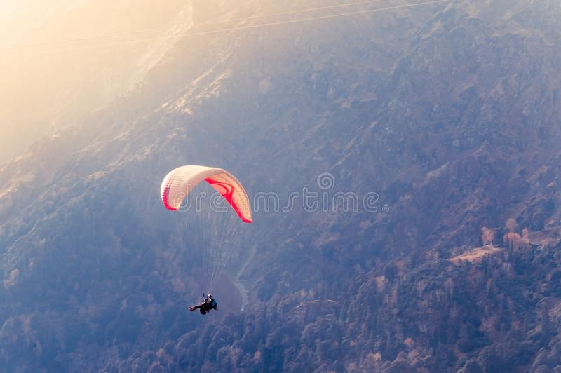 Close up of a Flying colorful parachute paragliding on beautiful mountain background. Solang Nullah, Kullu District, Manali Tehsil. Hill area, Himachal Pradesh royalty free stock image