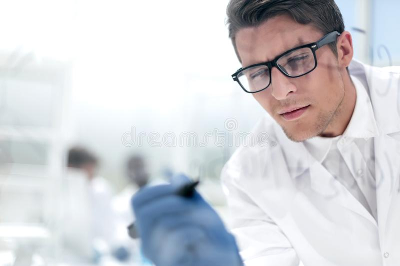 Close up.a focused scientist makes notes on the Board. Photo with copy space royalty free stock images