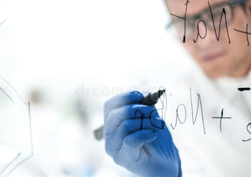 Close up.a focused scientist makes notes on the Board. Photo with copy space royalty free stock photo