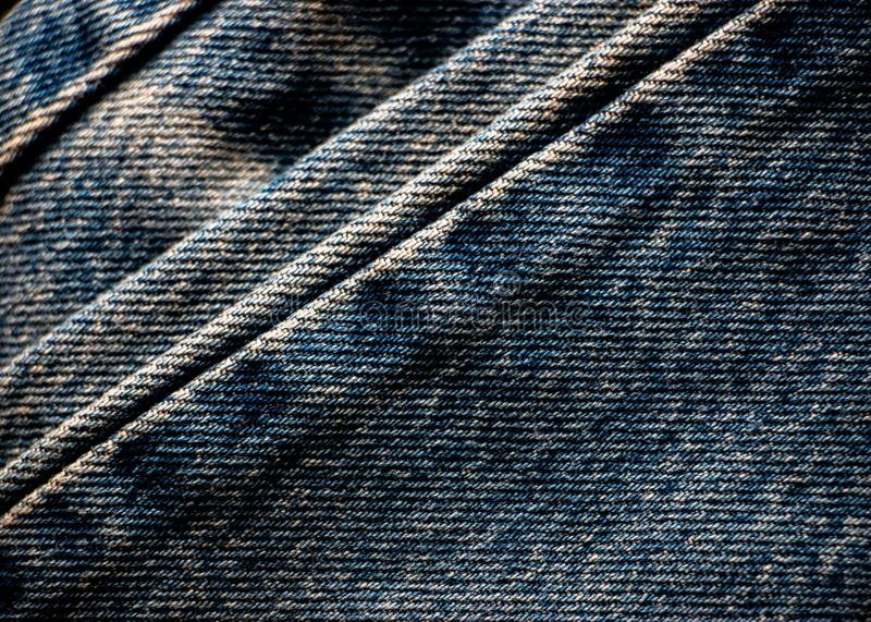 Close up of fold dark blue jean denim fabric. Texture as background royalty free stock image