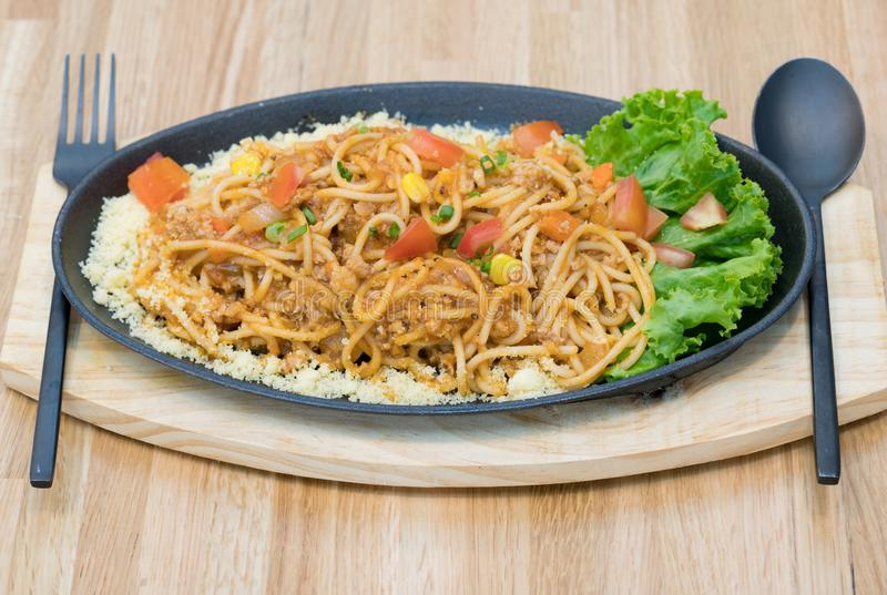 Close up food : Delicious Spaghetti with minced meat and vegetables. top view on wooden table with spoon and fork. stock photo