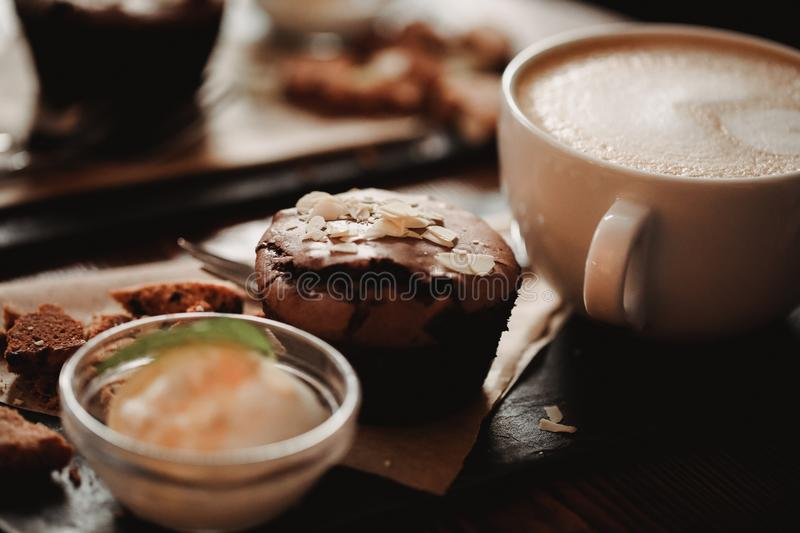 Close up food image of cup of coffee and dessert on the wooden table background in cafe. Trend warm toning. Photo with a small dep. Close up food image of cup of stock photos