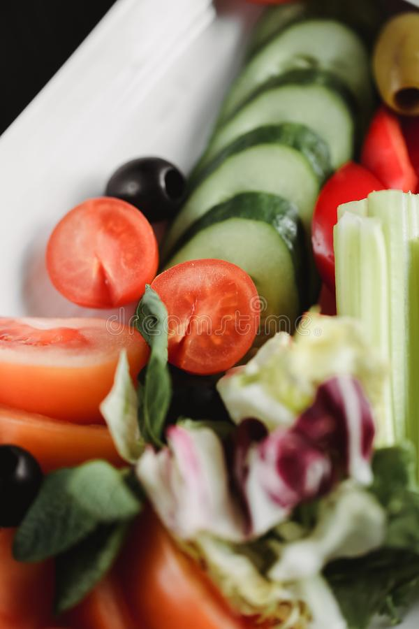 Close up food image of vegetables salad on white plate. Macro food photography of healthy meal. Focus on tomatoes.  royalty free stock photography