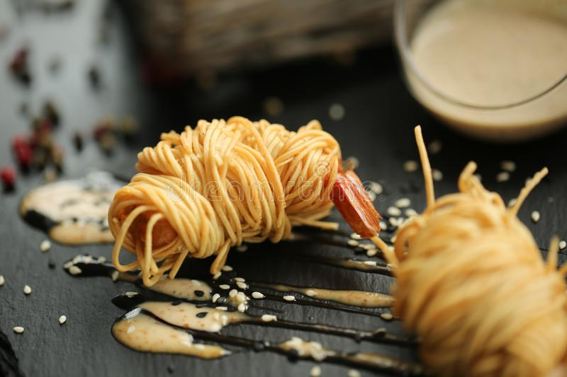 Close up food photo of fried tiger prawns in egg noodles on black slate background. Asian culture and cuisine. Food image of shrim stock photography