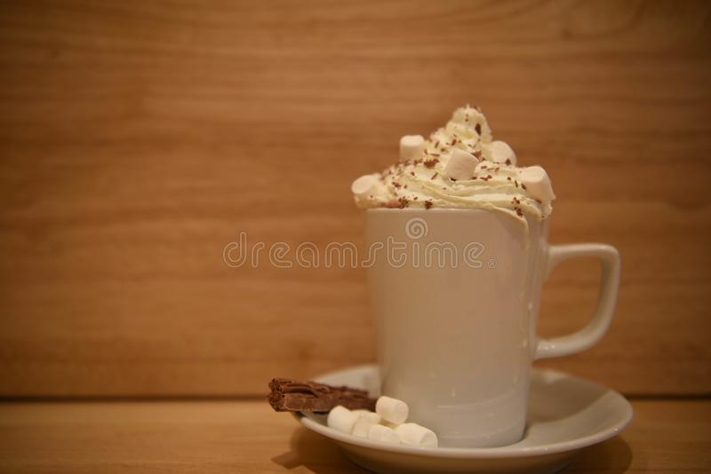 Close up food photography image of a hot chocolate drink in a cup and saucer with cream and marshmallows on wood background stock images