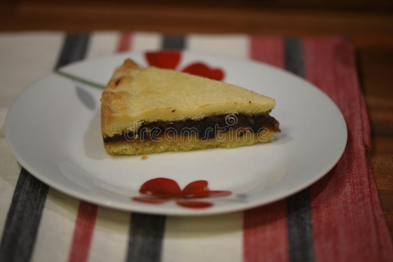 Close up food photography of traditional English homemade eccles tart made with currents and pastry on a table cloth background. A slice of traditional English stock photo