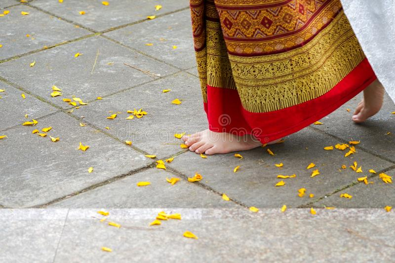 Close up foot step of Thai female dancing, with   yellow flower on floor stock image