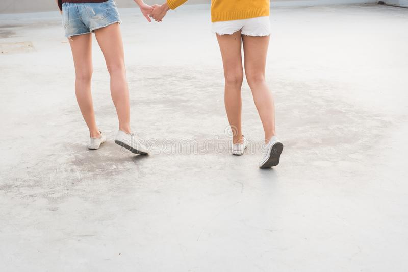 Close up foot of two woman holding hand and walking together. stock photo
