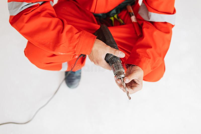 Close up foreman in orange work clothes holding drill machine in royalty free stock photography