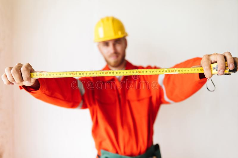 Close up foreman in work clothes and yellow hardhat holding meas. Close up foreman in orange work clothes and yellow hardhat holding measuring tape over white stock photos