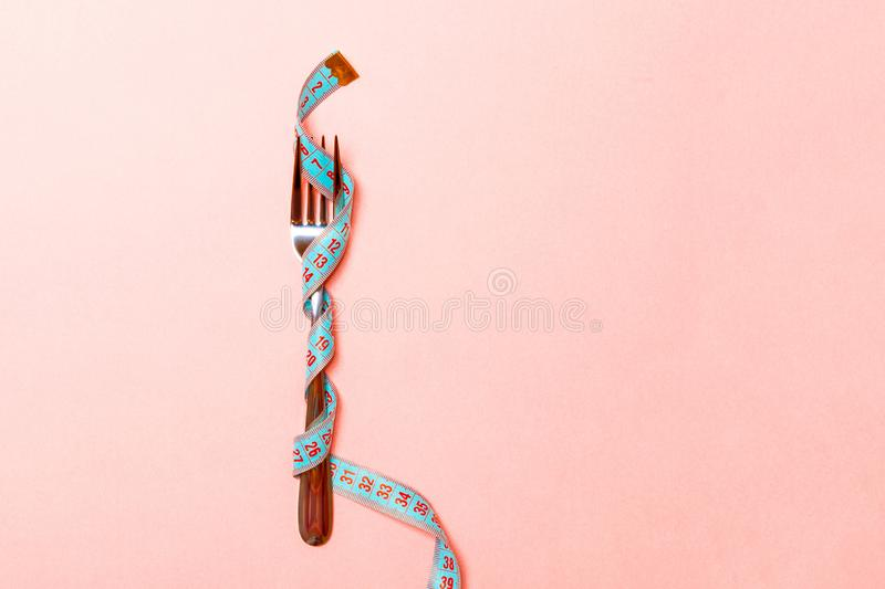 Close up of fork wrapped in measuring tape on pink background. Overweight and overeating concept stock images