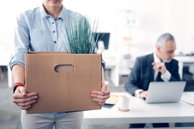 Close up of former employee holding box with office supplies. Bad ending. Cropped shot of a paper box full of different stuff held by a female office worker in stock photos