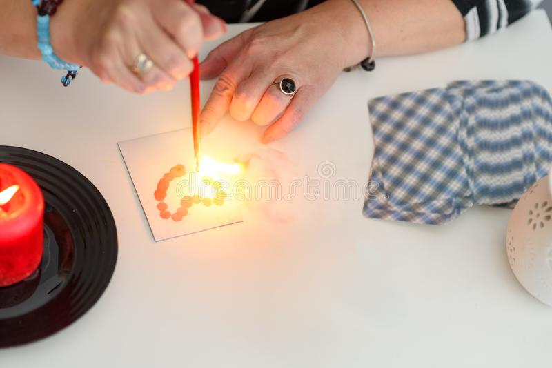 Close up of fortune teller woman hands make magic love spells. Fortune teller wonders on the candle, fortune teller make magic love spells. Mystical psychic stock images