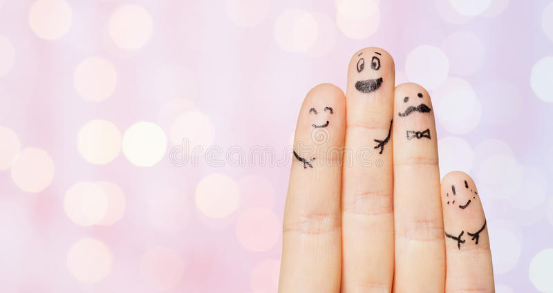 Close up of four fingers with smiley faces. Gesture, family, people and body parts concept - close up of four fingers with smiley faces over pink holidays lights royalty free stock photos