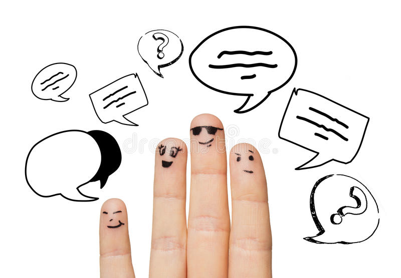 Close up of four fingers with text clouds. Communication, family, people and body parts concept - close up of four fingers with different facial expressions and stock photo
