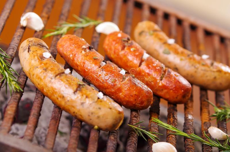 Close up of four grilling sausages on barbecue grill with some species. BBQ in the garden. Bavarian sausages.  royalty free stock image