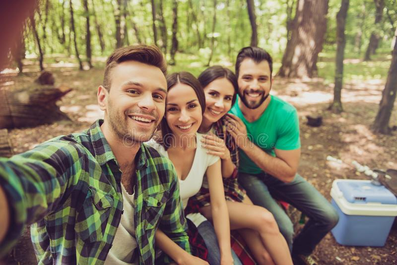 Close up of four happy friends tourists in the spring nice wood, embracing, posing for a selfie shot, that handsome blond guy is royalty free stock photo