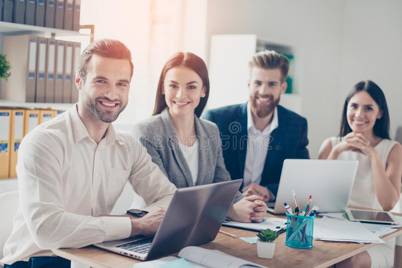 Close up of four successful young office workers looking straight and smiling, wearing smart formal wear in bright sunny stock image