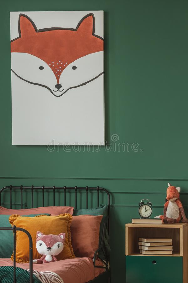 Close-up of a fox painting on a green wall above an orange and black bed for a child in a bedroom interior with plush fox toys. royalty free stock photography