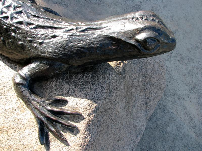 Close up fragment of bronze lizard sculpture on the big stone stock photo