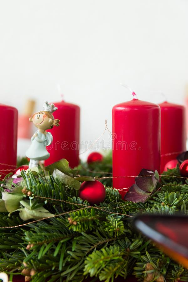 Close up fragment of Christmas wreath from fresh green fir tree branches decorated with red ornament baubles angel figure garland royalty free stock images