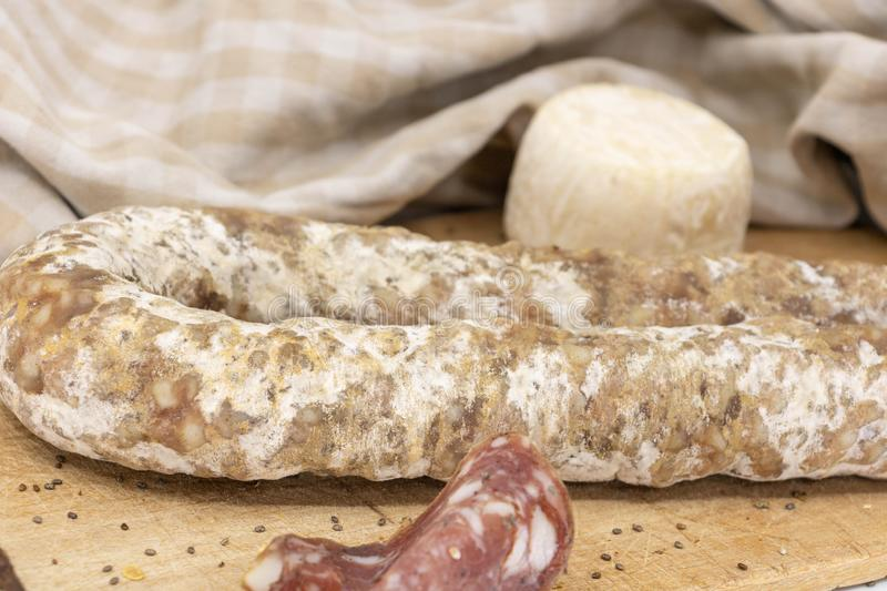 Close-up french charcuterie and goat cheese - preparation of a snack. TV or tasting platter on the theme of French charcuterie, Corsican charcuterie, and cheeses royalty free stock image