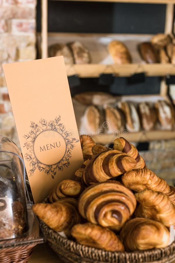 Close up of fresh baked croissants in wicker basket. With menu royalty free stock image