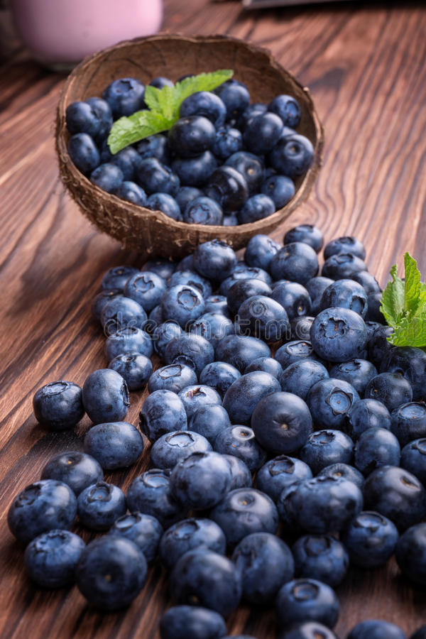 Close-up of fresh and bright blueberry in a wooden crate. Healthy, ripe, raw and bright dark blue berries on a wooden background. stock images