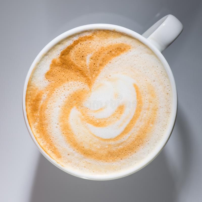 Close-up cup of coffee with little art, flat lay. Close-up fresh coffee with little art on the foam in a white ceramic cup on a white surface, flat lay royalty free stock images