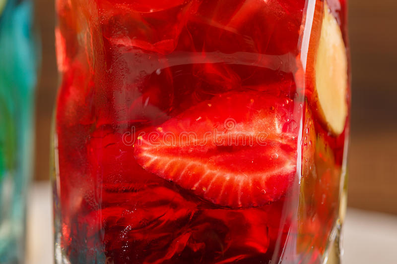 Close-up of fresh colorful cocktail with strawberry, ginger and ice on a wooden background. Refreshing summer beverages. stock photo