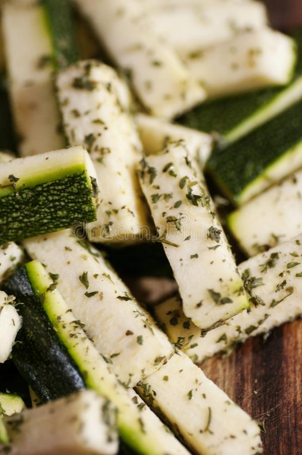 Fresh cut seasoned zucchini on wood. Close-up of fresh cut seasoned zucchini on wood with provencal spices stock images