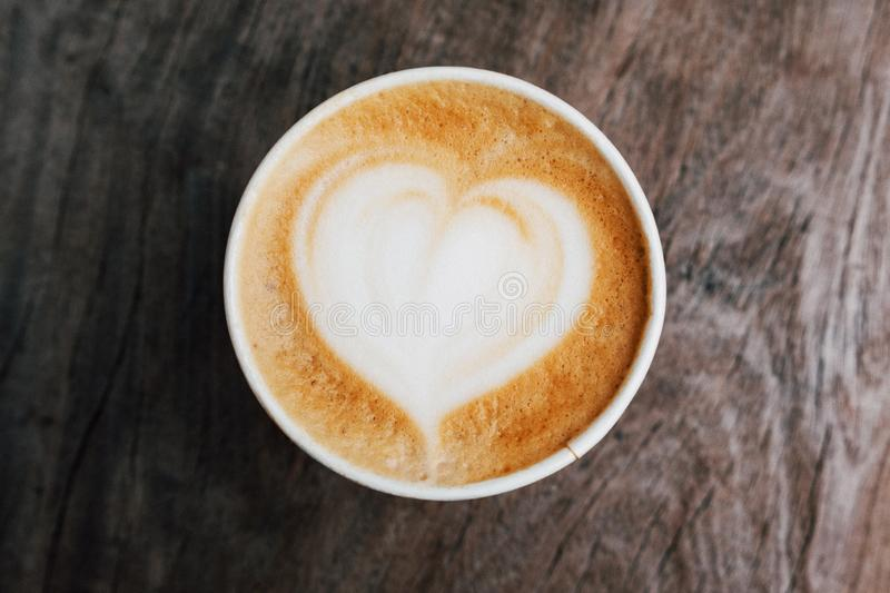 Close up of fresh delicious cappuccino coffee with beautiful latte art in the shape of heart on dark wooden background. stock image