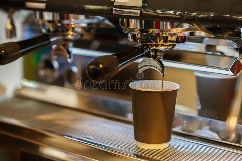 Close-up fresh espresso pours in paper cup, Italian espresso machine. Coffee culture and professional coffee making royalty free stock image