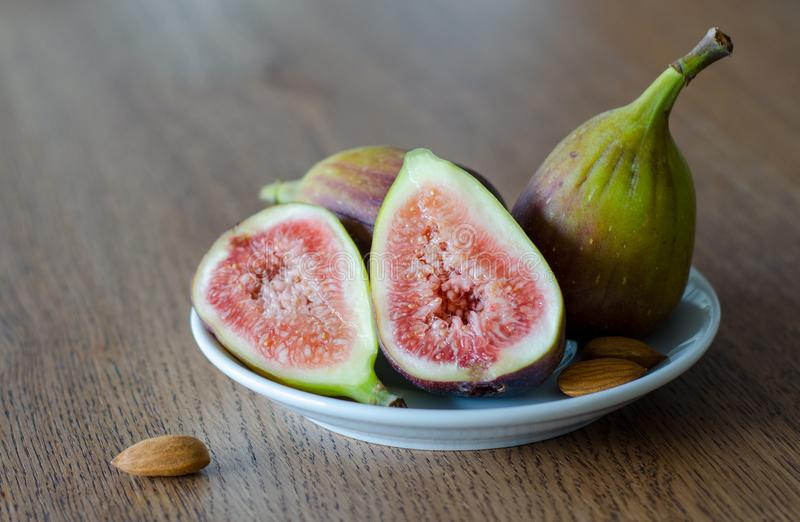 Close-up of fresh figs with one slised ripe fig and three almond nuts lying on white plate on a wooden table background stock photography