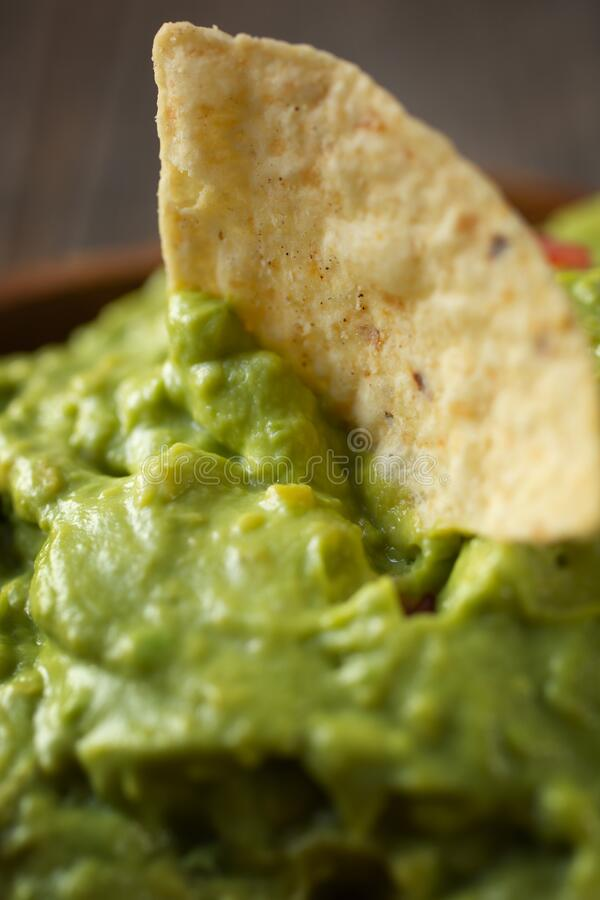 Close up of fresh guacamole with nachos chips royalty free stock images