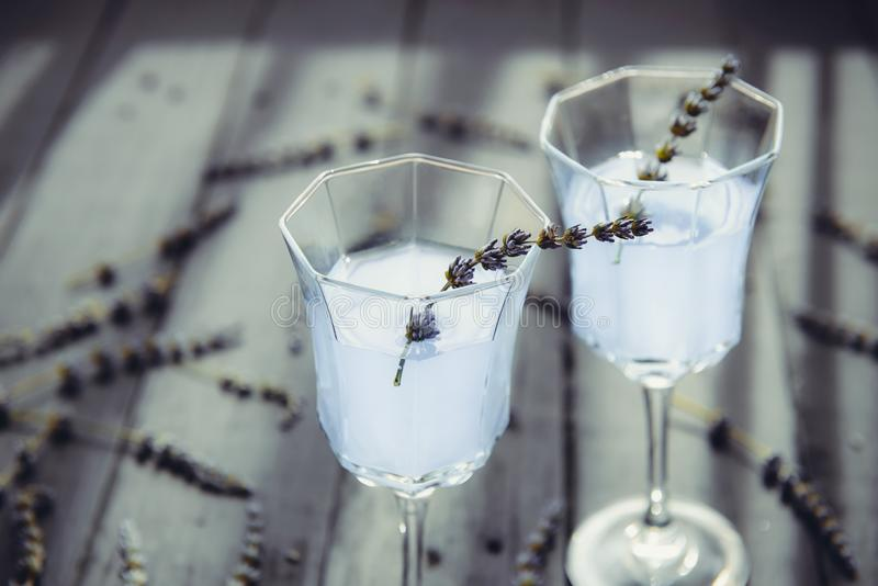 Close up Fresh lavender lemonade with flowers in beautiful glasses on dark wooden table in back light. Detox water. Summer drink. Diet cocktail. Selective royalty free stock photos